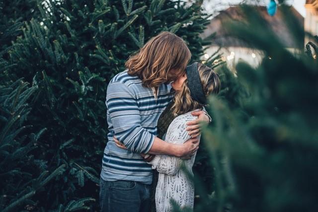 Et par kysser blandt grantræer.